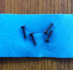 """Figure 2: The case screws after removal. For scale, the blue tape is 7/8"""" wide."""