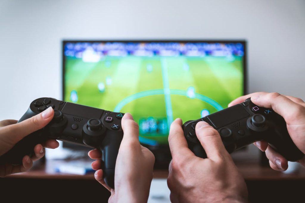 Image of hands playing two video game controllers in the foreground with a television farther away