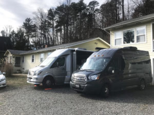 Two class B RVs parked in front of a home