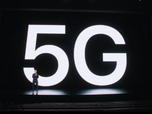 Tim Cook in from of a 5G sign at the Apple iPhone event